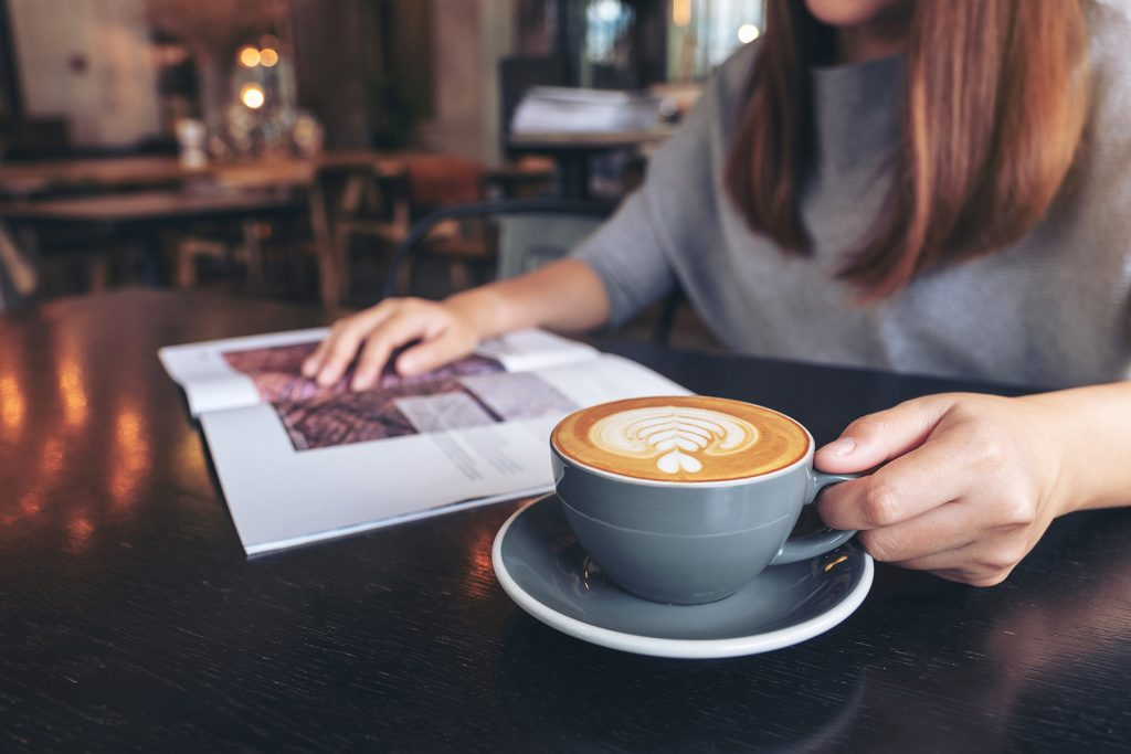 Image of a woman reading a magazine while drinking a latte.